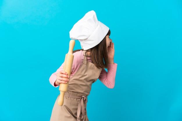 青い壁に隔離された麺棒を持った少女が口を大きく開いて叫んでいる