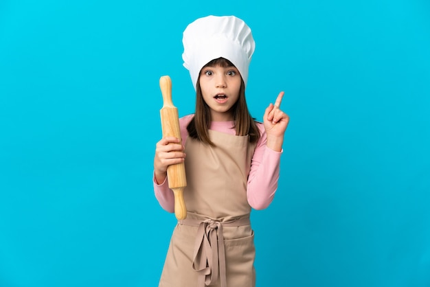 Маленькая девочка держит скалку, изолированную на синей стене, думая об идее, указывая пальцем вверх