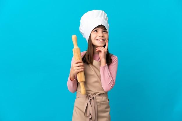 찾고있는 동안 아이디어를 생각하는 파란색 벽에 고립 된 롤링 핀을 들고 어린 소녀