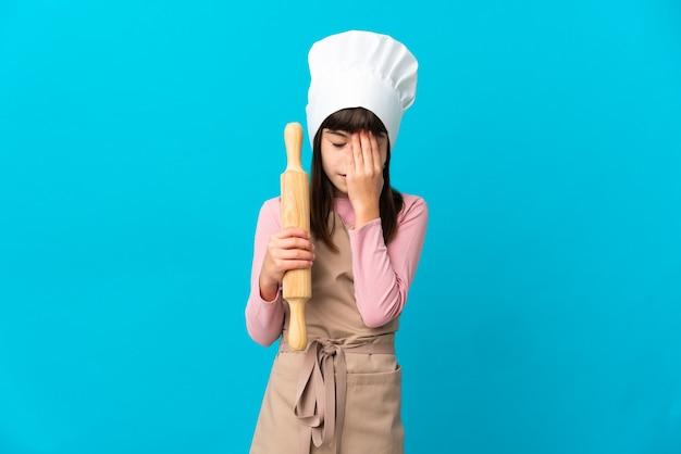 疲れて病気の表情で青い壁に分離された麺棒を保持している少女