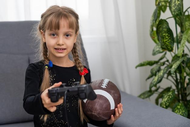 ビデオゲームをプレイするためのラグビーボールとジョイスティックを持っている少女