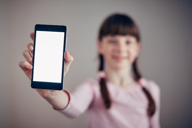 어린 소녀 흰색 스크린 스마트 폰 들고