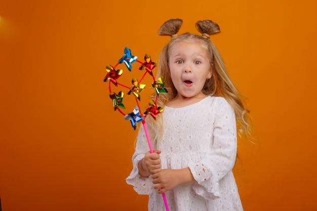 黄色い空間におもちゃの風車を持っている少女