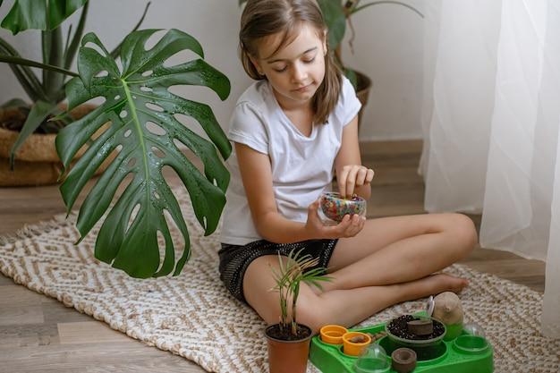 식물 장식을 위한 장식용 멀티 컬러 물 구슬이 있는 꽃병을 들고 있는 어린 소녀.