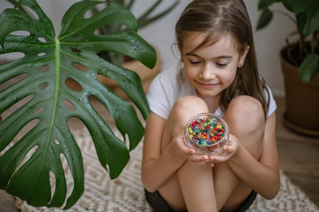 여러 가지 빛깔의 장식 물 구슬이 있는 꽃병을 들고 있는 어린 소녀.