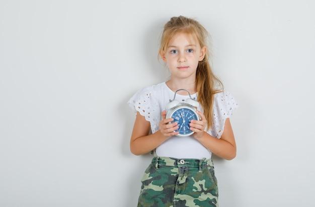 白いtシャツで目覚まし時計を保持している小さな女の子