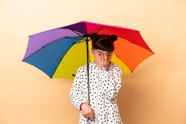 피곤하고 아픈 표정으로 베이지 색 배경에 고립 된 우산을 들고 어린 소녀