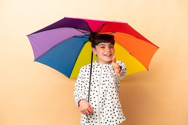좋은 거래를 닫기 위해 악수하는 베이지 색 벽에 고립 된 우산을 들고 어린 소녀