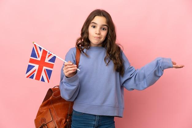 Маленькая девочка держит флаг соединенного королевства на розовом фоне, сомневаясь, поднимая руки