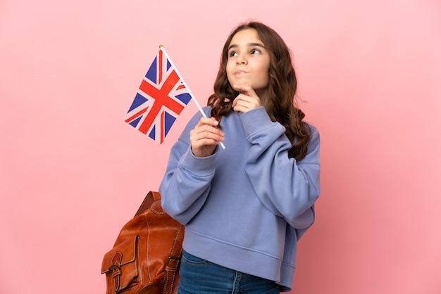 Маленькая девочка держит флаг соединенного королевства, изолированные на розовом фоне, сомневаясь
