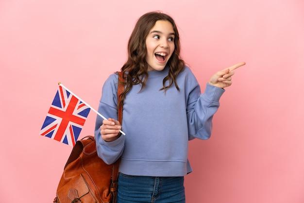 Маленькая девочка держит флаг соединенного королевства на розовом фоне, намереваясь реализовать решение, подняв палец вверх