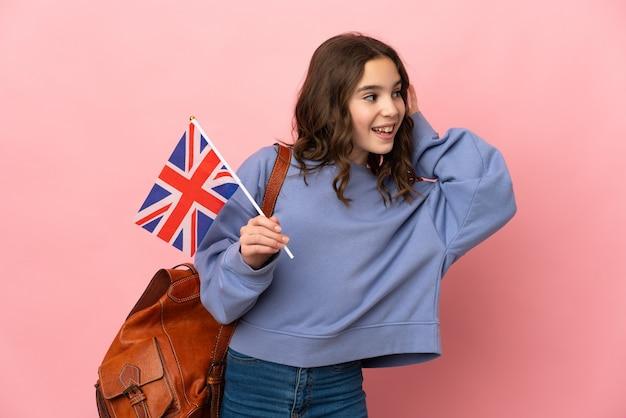 귀에 손을 넣어 뭔가를 듣고 분홍색 배경에 고립 된 영국 국기를 들고 어린 소녀