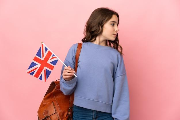 横を見てピンクの背景に分離されたイギリスの旗を保持している少女