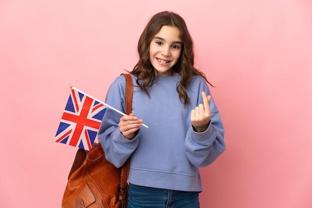 Маленькая девочка держит флаг соединенного королевства, изолированные на розовом фоне, делая денежный жест