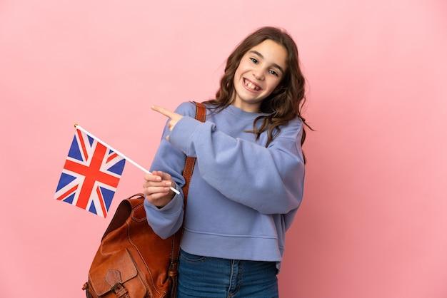 Маленькая девочка держит флаг соединенного королевства, изолированные на розовом фоне, указывая назад