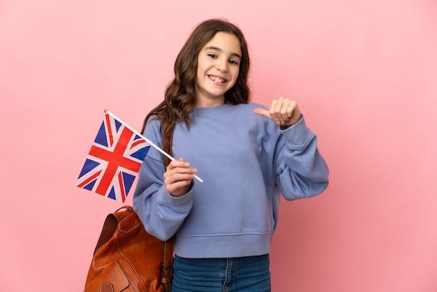 誇りと自己満足のピンクの背景に分離されたイギリスの旗を保持している少女
