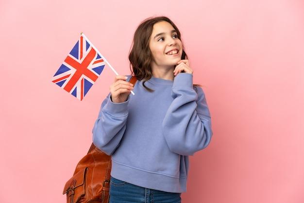 Маленькая девочка держит флаг соединенного королевства на розовом фоне, думая об идее, глядя вверх