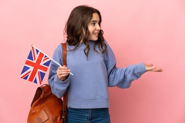 측면을 보면서 깜짝 표정으로 분홍색 배경에 고립 된 영국 국기를 들고 어린 소녀