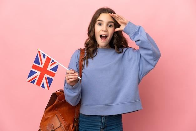 놀라운 표정으로 분홍색 배경에 고립 된 영국 국기를 들고 어린 소녀