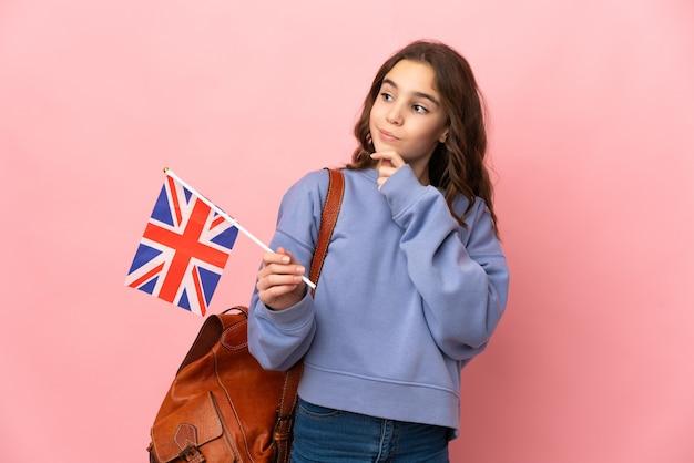 Маленькая девочка держит флаг соединенного королевства на розовой стене и смотрит вверх