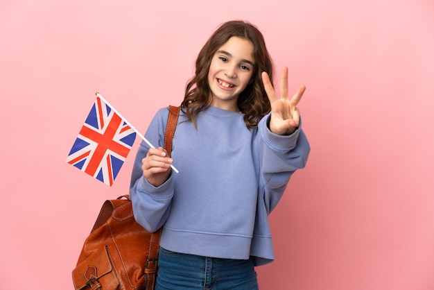 핑크 벽 행복에 고립 된 영국 국기를 들고 손가락으로 세 세 어린 소녀