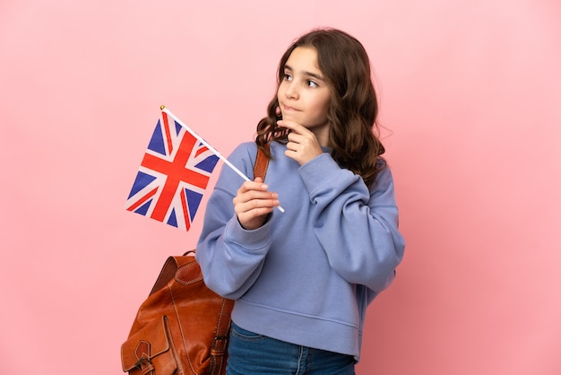 Маленькая девочка держит флаг соединенного королевства, изолированную на розовой стене, сомневаясь и думая