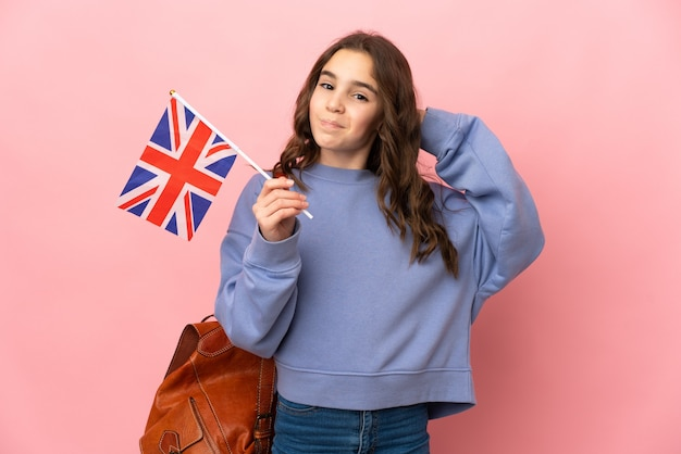 Маленькая девочка держит флаг соединенного королевства, изолированную на розовой стене, сомневаясь