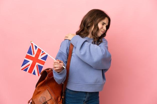 Маленькая девочка держит флаг соединенного королевства, изолированную на розовой стене, страдает от боли в плече из-за того, что приложила усилие