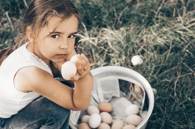 Маленькая девочка держит и собирает качественные органические яйца хорошего качества и привлекает внимание на ферме.