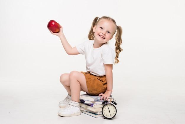 Bambina che tiene mela seduta su una pila di libri isolati