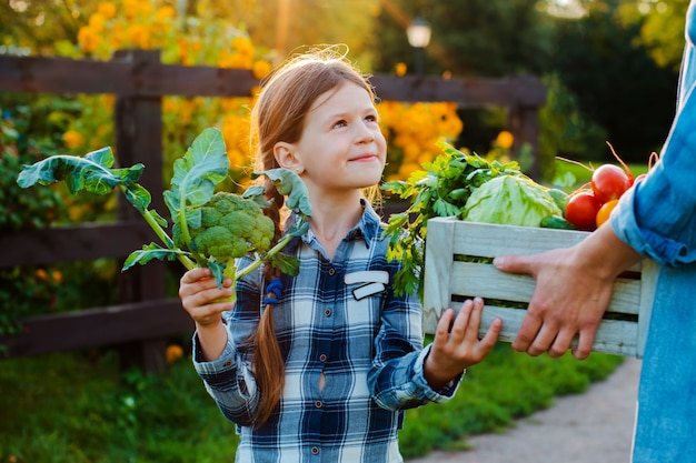 Little girl holding a basket of fresh organic vegetables with her mom