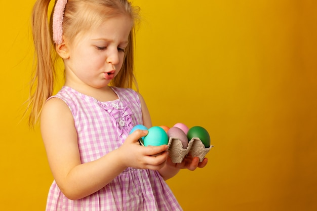 Little girl holding basket with colored eggs. easter concept