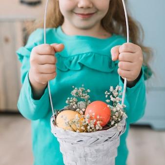 Little girl holding basket with easter eggs