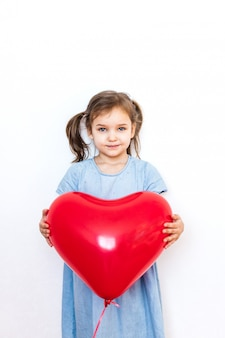 Little girl holding a beautiful red heart-shaped balloon for a gift for valentine's day, lovers, valentine's day, family and heart