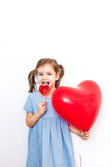 A little girl holding a beautiful red heart-shaped balloon for a valentine's day gift and a lollipop in the shape of a heart, lovers, valentine's day, family and heart