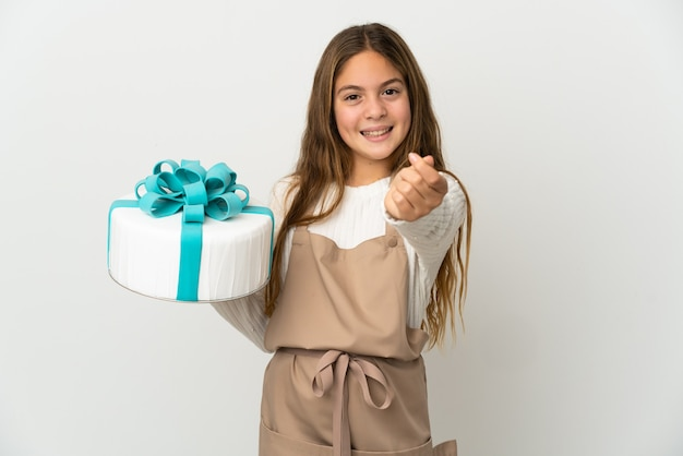 Little girl holding a big cake over isolated white background making money gesture