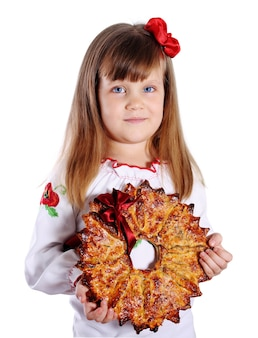 Little girl holding big christmas star, a traditional dessert. ukrainian kalita