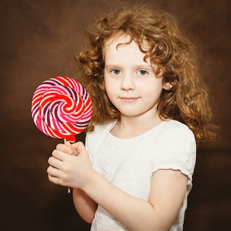 Little girl holding big colorful lollipop, toning in brown.