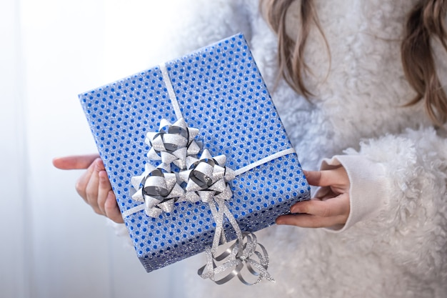 A little girl holding a blue holiday gift.
