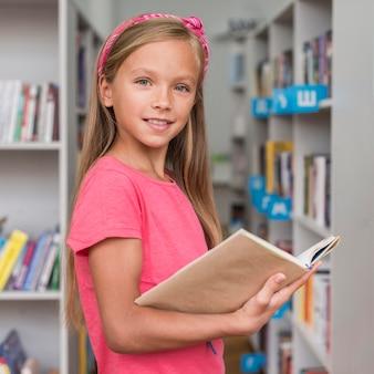 Bambina che tiene un libro in biblioteca