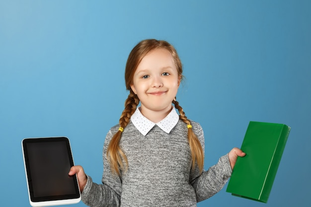 Little girl holding a book and tablet.