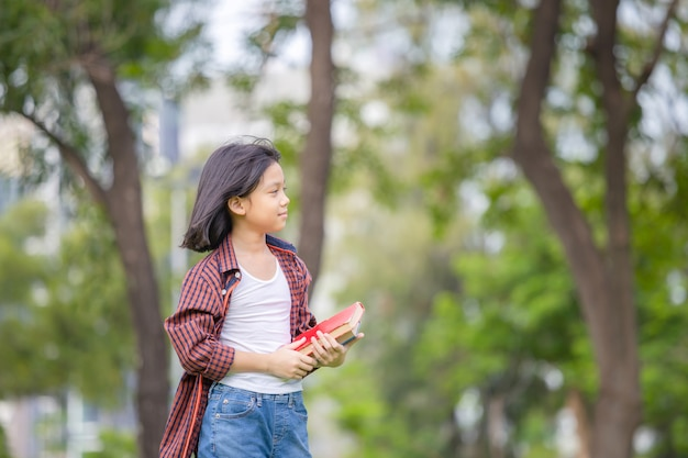 Little girl holding a book and walking in the park