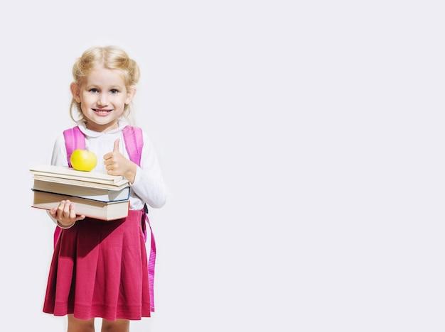 책과 사과를 들고 흰색 배경에 고립 된 확인 서명을하는 어린 소녀