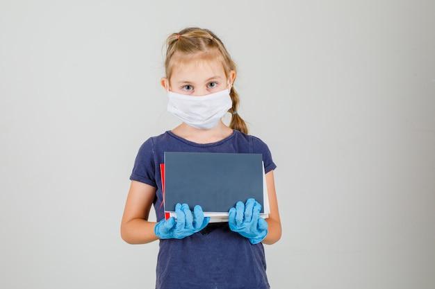 Libri e taccuini della tenuta della bambina in maglietta, guanti e vista frontale della maschera medica.