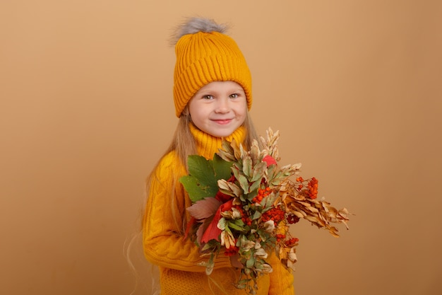 Little girl holding a bouquet of autumn leaves on a beige space , smiling