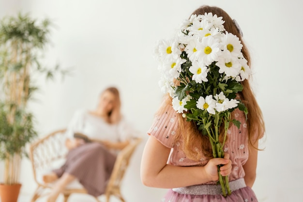 Little girl holding bouquet of spring flowers as a surprise for her mother