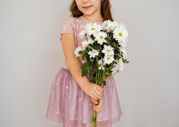 Little girl holding bouquet of spring flowers