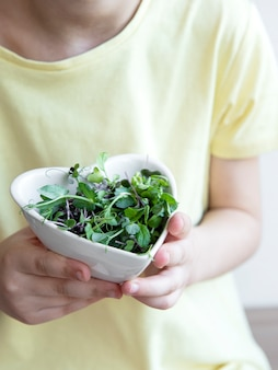 Little girl holding a bowl with microgreens in her hands. healthy eating concept