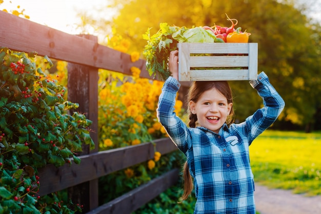 Little girl holding box of fresh organic vegetables