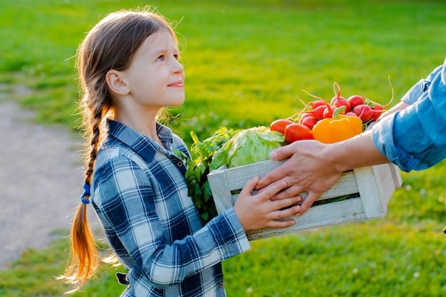 Little girl holding box of fresh organic vegetables